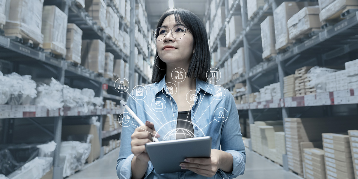 businesswoman reviewing the inventory in a warehouse using a tablet