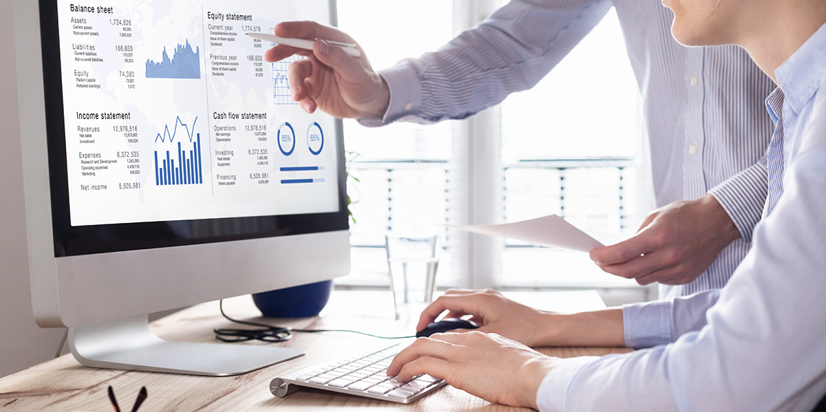 two coworkers reviewing financial report on a computer screen