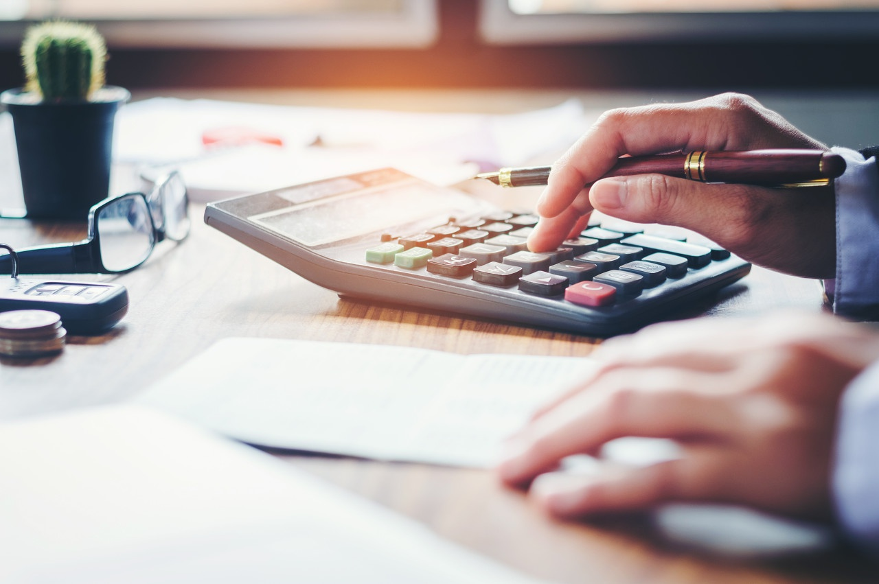 close up of man using calculator with a pen in his hand