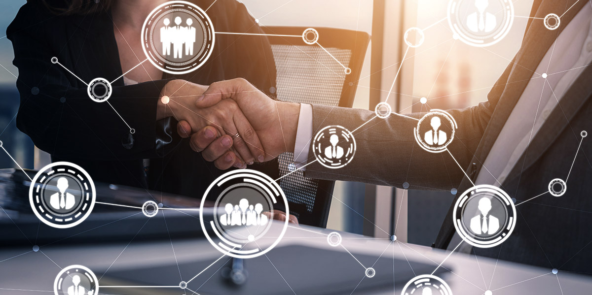 two business people shaking hands with an overlay of networking icons