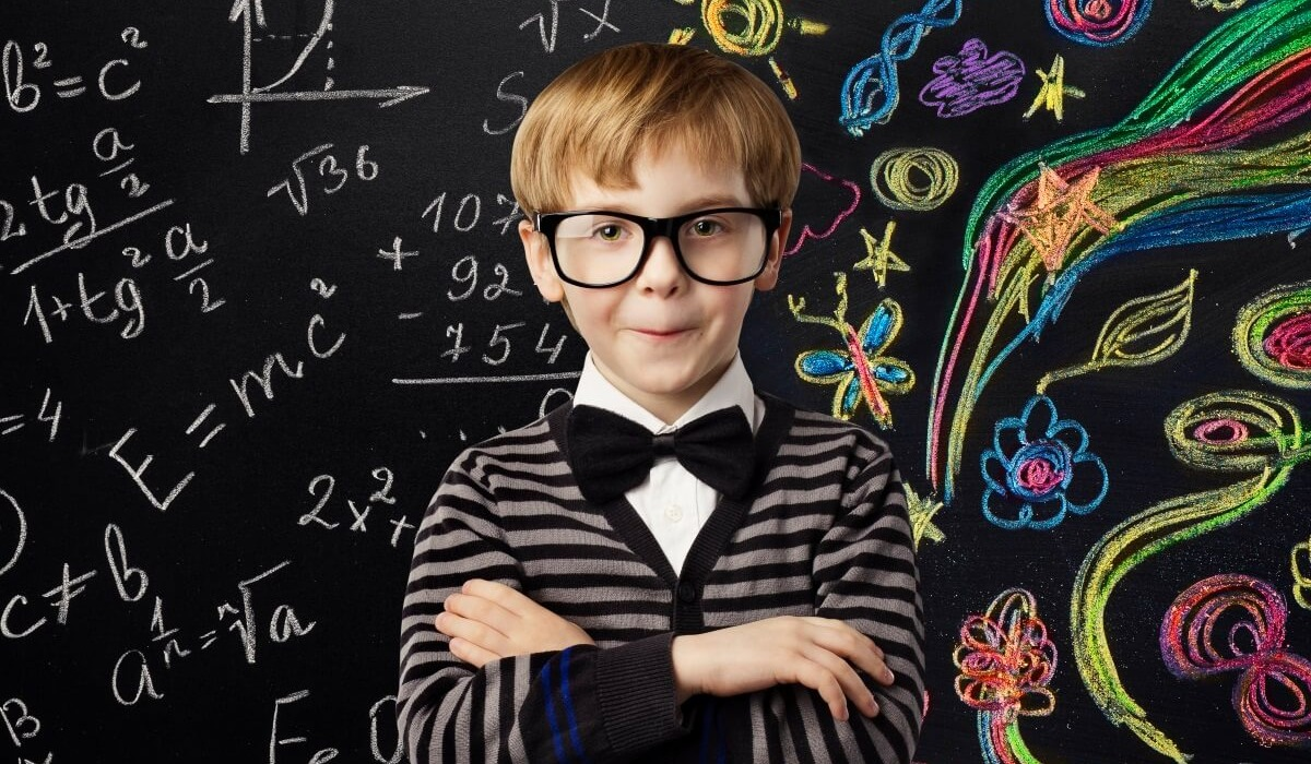 bespeckled child standing in front of a chalk board filled with equations and doodles