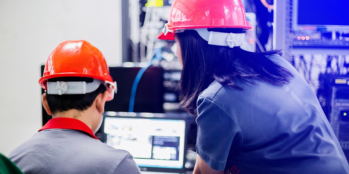 two employees in hardhats conversing in front of a computer